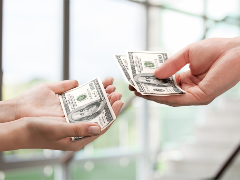 Hands exchanging money for debt settlement fees