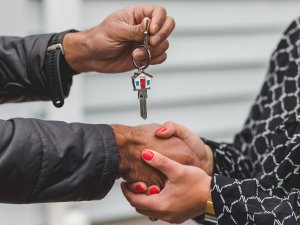 This is a person handing a key for a housing market property.